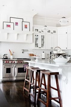 Amazing kitchen features white cabinets with oil-rubbed bronze hardware paired with white marble countertop and white…
