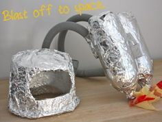 How to make an astronaut costume - use foil and silver duct tape for jet pack.  Attach bottles to a square of cardboard covered in foil, then run ribbon through for straps.