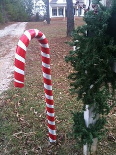 Pool Noodle Candy Cane  covered the pool noodle in white duct tape, then went back with red for the candy cane effect. The curve was made and held in place by clear fishing line. A rebar post (steel or iron post) was put into the ground, and the noodle slipped over the post.