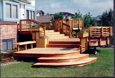 Multi-level redwood deck with unique round shaped steps and built-in planter boxes designed by @DeckTec Outdoor Design  | followpics.co