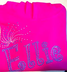 Ellie hoodie, written in the bubbly Curlz font with a beautiful bling spray. Done in a mixture of aqua rhinestuds and clear rhinestones to contrast against the hot pink hoodie. This kind of product can be fully personalised with different fonts/designs and colours of diamontes. For more info please visit our website or give us a call!