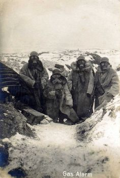 Four German soldiers wearing fur coats and gas masks in a trench, 1917.