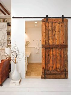 I would love to do this for the entryway between the kitchen and dining room ... old barn door on a track system.
