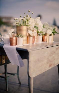 """Rose gold spray painted tin cans to line the pavement. lowercase """"r"""" punched into it with a candle inside."""