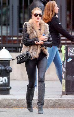 Rosie Huntington Whiteley usa look de jaqueta e calça de couro com colete de pelos e bota de cano alto cinza