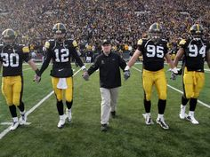 Honorary captain Dan Gable takes the field with Iowa team captains Brett Greenwood, Ricky Stanzi, Karl Klug and Adrian Clayborn, for the coin toss, before the Ohio State game, Saturday, Nov. 20, 2010, at Kinnick Stadium, in Iowa City.