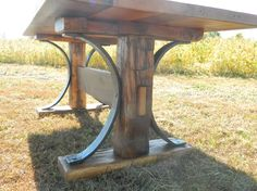 A neat old farm table. Original hand hewn uprights from an old granary. Amazing workmanship from a real blacksmith hammering out 3/4in x 3in curves to bring the table together. Wonderful reclaimed white oak top full of character and variation. AntiqueWoodworks.com