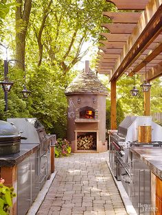 Outdoor Kitchen Plus - A galley-style kitchen equipped with all the bells and whistles lines up along a stone pathway leading to a focal-point wood-burning oven that also serves as a fireplace. Most any recipe can be cooked up using the pizza oven, gas burners, grill, smoker, or rotisserie. Stainless-steel cabinets and stone countertops enhance the kitchen's purpose and good looks.