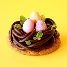 Chewy choc chip cookies topped with a chocolate ganache birds nest and speckled eggs in the centre.