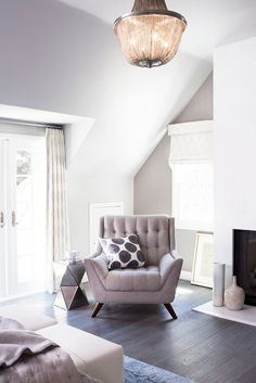Grey fabric armchair with a geometric mirrored side table and a chandelier complete this seating area.