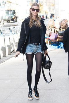 Behati Prinsloo holds onto a summer staple—adding tights under her cut off shorts and a shearling jacket.