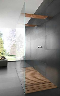 Stunning bathroom design with timber shower base and charcoal tiles. Large space with large floor to ceiling window.