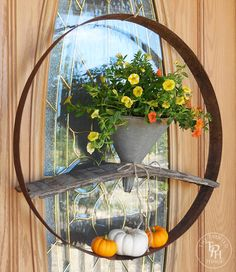 DIY tutorial to make a gorgeous Fall wreath by repurposing a funnel and a wine barrel! The funnel part acts as a vase for Fall flowers or whatever you like!