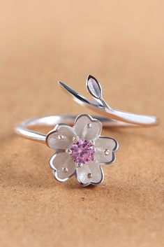 This beautifully crafted and minimalist cherry blossom ring is made from sterling silver and will stand out on any hand. The flower is set with a girlish pink stone, and the band is made to look li… Simple Jewelry, Cute Jewelry, Body Jewelry, Jewelry Shop, Jewelry Art, Jewelry Accessories, Jewelry Design, Fashion Jewelry, Delicate Jewelry