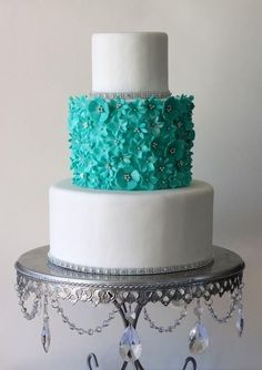 Wedding cake with white and teal.. One layer covered with tiny flowers, two plain white tiers bordered in rhinestones