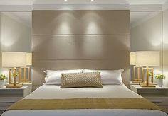 Cabeceira de tecido ou couro bege com costuras na horizontal + espelho do piso ao teto (para aumentar o quarto que é pequeno) + criados brancos.