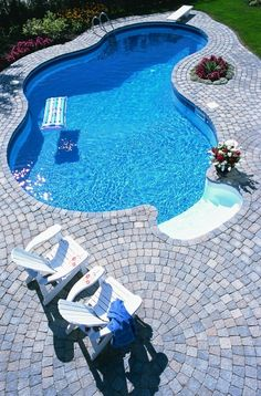Cool Stone Pool Deck Design Ideas with Twin White Chair on Stone Pool Deck in Simple Shape Swimming Pool