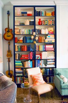 Hanging guitars next to navy bookcase by Little Green Notebook