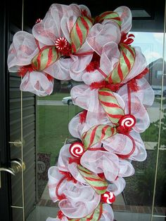 This is a red candy cane wreath with white/red poly mesh ribbon, and has a green and red candy cane glitter ribbon. This also has candy picks