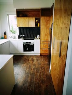 Ply and chalk white cabinets, hexagonal tile backsplash. Vinyl floor boards. NZ.