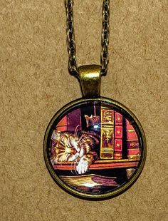 Cat on shelf with antique books. Pendant necklace Bronze tone chain.                                                                                                                                                                                 More