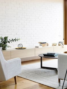 The living area features white-painted brick party walls and floating timber joinery.