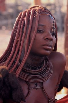 Himba woman in Namibia. The Himba use red ochre to color their skin and hair. Much safer than chemical hair dyes.