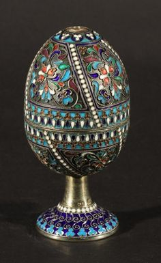 """RUSSIAN SILVER GILT & CLOISONNE ENAMEL CONVERTIBLE EGG, MAKER'S MARK """"AG"""", MOSCOW, CIRCA 1908-1926 ENAMELED WITH POLYCHROME STYKIZED FOLIAF=GE,VTHE INTERIOR WITH FITTINGS FOR CONVERSION TO EGG CUPS"""