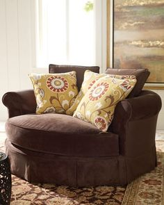"""A """"cuddle chair"""". Who doesn't want one of these in a nice linen, or a bold print minus the tacky pillows."""