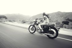 The lovely Jeannette Mekdarariding a vintage Triumph motorcycle through rolling desert hills. Photograph by Peter Dawson. [ more photos of Jeannette | Triumphs ]