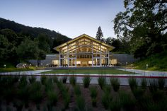 The central gable and large window wall front onto an inviting terrace and lawn while the flanking support wings, sheltered under green roofs, connect to the adjacent hillsides with board-form concrete walls - Branson School Student Commons, Turnbull Griffin Haesloop Architects