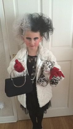 dressed as Cruella De Vil from 101 Dalmatians. Black dress and tights, old white beads, black handbag. Eyeliner for eyebrows, old winter fur coat. Lots of back combing and hair spray finished with hair spray colours Book Costumes, World Book Day Costumes, Book Week Costume, Dress Up Costumes, Fancy Dress Design, Fancy Dress For Kids, Storybook Character Costumes, World Book Day Ideas, Children's Book Characters