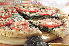 A pizza crust is spread with a mix of spinach and Gorgonzola, topped with mozzarella, tomato slices and more Gorgonzola cheese then baked until golden.