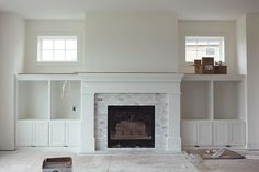 Fireplace with marble subway tiles and Windows above the built-ins Fireplace Windows, Fireplace Redo, Fireplace Built Ins, Fireplace Remodel, Brick Fireplace, Living Room With Fireplace, Fireplace Surrounds, Fireplace Design, My Living Room