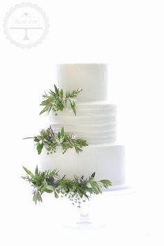 A simple and natural wedding cake decorated with olive leaves and herbs