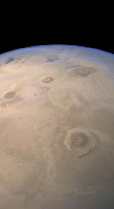 The Mars Express High Resolution Stereo Camera (HRSC) captured this view of Mars' Tharsis volcanic region on June 29, 2014 during its 13,323rd orbit of the planet. This image uses low-resolution blue, green, and IR color data (with green and IR blended 50-50 to produce a synthetic red image) overlaid on a high-resolution clear filter image. Olympus Mons is at center. Across top center from left to right are Ascraeus Mons, Pavonis Mons, and Arsia Mons. Noctis Labyrinthus can be seen near the…
