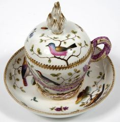 A Berlin porcelain chocolate cup cover and stand, 19th century, the relief moulded cup decorated with birds, foliage and insects, and a ribbon in relief forming the handle, the domed cover with conforming decoration and flame finial