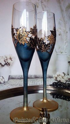 Conjunto de 2 copas de champaña pintadas a mano con delicadas hojas de arce en oro y negro y efecto de escarcha muy otoñal.