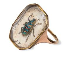 """About 200 years old, this weevil (Tetrabothynus regalis) has been set in a gold ring. The words appear to be: """"A phrase taken from Virgil's Georgics: 'Admiranda tibi levium spectacula rerum' - 'I'll tell of tiny things that make a show well worth your admiration'."""""""