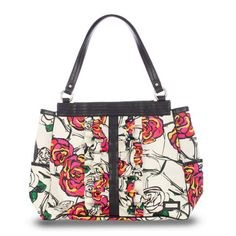 Katy (prima)- It's your time to bloom! The Katy Shell for the Prima Bag is like a bouquet from an enchanted garden, complete with abstract rose print in bold shades of red, pink, yellow and green. Tuxedo ruffles on the front and black trim details add just the right amount of sophistication to this unique Shell. Whether you're headed to a garden party or to an art gallery, you'll look stunning.