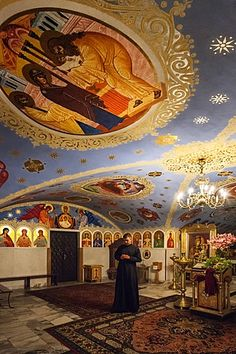 Priest stands under ceiling frescoes in the Passion of Christ Chapel, basement of Maria Magdalena Polish Orthodox Cathedral, Warsaw, Poland, Europe