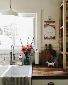 sink vignette: staggered cutting boards, calendar hung w/ a wooden hanger, dish soap & brush in ceramic berry basket, mason jar w/ fresh flowers, ...