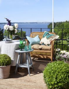Linen cloth from Heaven and the small table in the gray-painted rattan, loveseat in hand woven rattan, and beig ...
