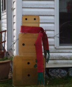 Plastic snowman sits by house