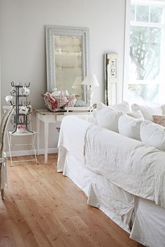 dreamy whites ~ white slip-covered couch - CHECK, gorgeous wood floors with character - CHECK, amazing natural lighting - CHECK