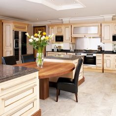 Kitchen-diner with stone flooring, pale-wood Knole cabinetry with wooden table