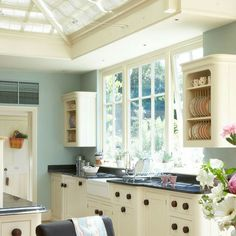 I think the black granite and ebony door knobs look amazing in this country kitchen