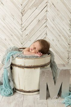 Newborn baby boy sleeps in a bucket next to a large letter M, Orange County photographer, baby studio, props, ideas, inspiration, boutique, Costa Mesa photography, GilmoreStudios.com