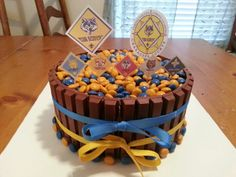 Cub Scout blue and gold cake. Double layer cake surrounded by kit-kats and topped with M.