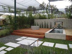 aménagement petit jardin avec bassin décoratif, allée en dalles, gravier décoratif et brise-vue en plantes